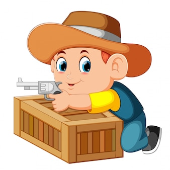 Smart cowboy holding his gun and behind the box