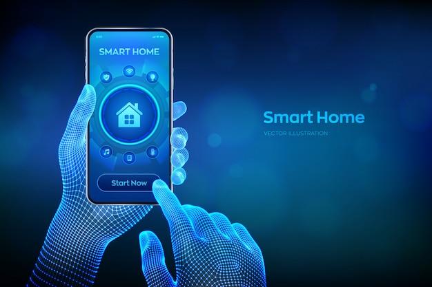 スマートホーム。仮想画面上の自動化制御システムの概念。ワイヤーフレームの手でスマートフォンをクローズアップ。