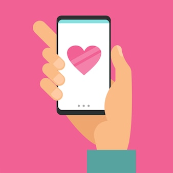 Smart phone in male hand with message big heart on pink
