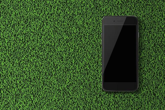 緑の草の背景に黒い画面とスマートフォン。