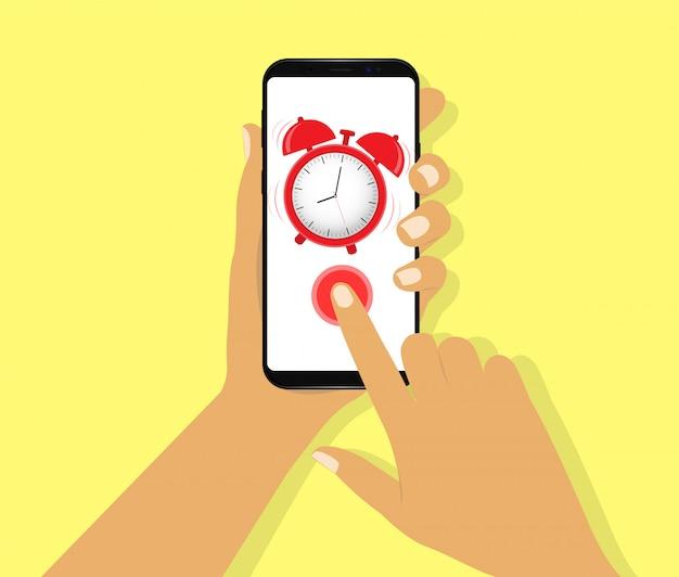 手で目覚まし時計を持つスマートフォン。目を覚ます。