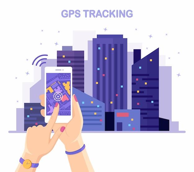 手に追跡するgpsナビゲーションアプリを備えたスマートフォン。夜の街並み、建物のある街並み