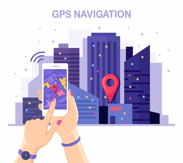 手に追跡するgpsナビゲーションアプリを備えたスマートフォン。夜の街並み、街並み