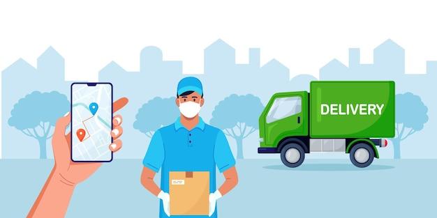 配達追跡食品または小包のためのモバイルアプリを備えたスマートフォン。カートンボックスを保持している顔のマスクと青い保護医療用手袋の配達人。トラックによる安全な配達サービス