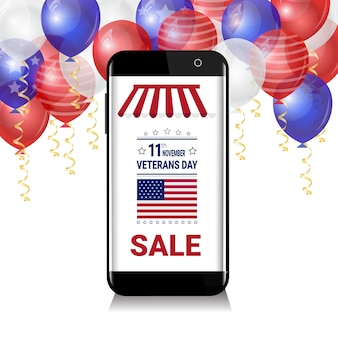 Smartphone with sale for veteran day message over white, blue and red balloons on background