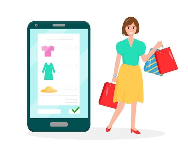 화면에 쇼핑 주문이있는 스마트 폰과 쇼핑백과 함께 행복한 여성.