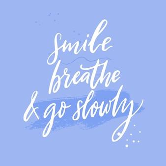 미소 짓고 숨을 쉬고 천천히 가십시오. 평온, 마음 챙김 및 느린 삶에 대한 영감을 주는 인용문. 파란색 배경에 흰색 필기 텍스트입니다. 동기 부여 말.