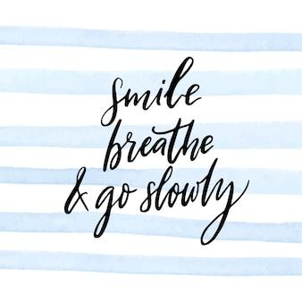 미소를 짓고 숨을 쉬고 천천히 가십시오. 평온, 마음 챙김 및 느린 삶에 대한 영감을 주는 인용문. 파란색 수채화 스트립 배경에 흰색 필기 텍스트입니다. 동기 부여.