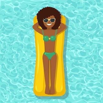 笑顔の女の子がプールのエアマットレスで泳ぐ