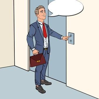エレベーターボタンを押すブリーフケースと笑顔のビジネスマン