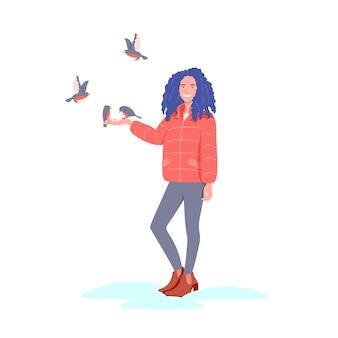 笑顔の女の子が冬に鳥に餌をやる