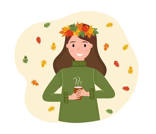 Улыбающаяся девушка в венке из осенних листьев с чашкой горячего напитка в руках падающие разноцветные листья