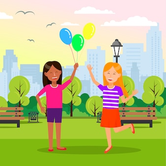 Smiling girls hold balloons in hands at city park.