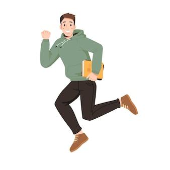 Улыбающийся парень в толстовке с капюшоном с книгой прыгает кулаком вверх