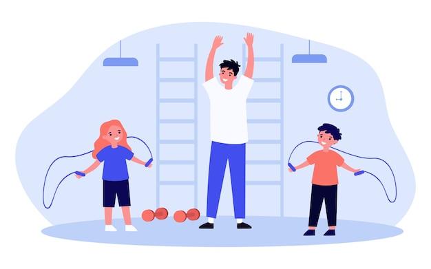 Улыбающиеся дети тренируются в тренажерном зале с тренером