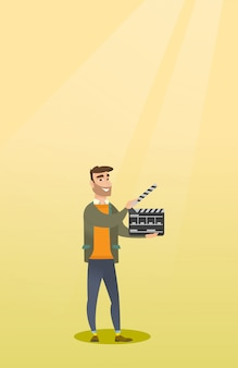 Smiling man holding an open clapperboard.