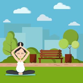 Улыбается беременная женщина, медитируя и расслабляясь в парке.