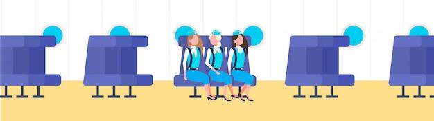 Smiling stewardesses team in blue uniform airplane attendants sitting on seats modern plane board interior female happy workers full length horizontal
