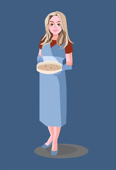 A smiling woman with blond hair in a dress holds a baking sheet with dough in her kitchen mittens