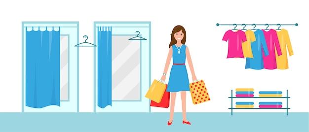 洋服を試着するためにキャビンの近くに買い物袋を持った笑顔の女性。