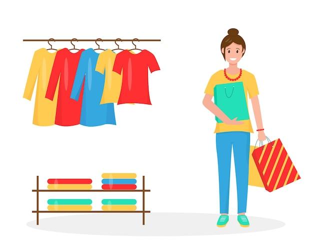 쇼핑백과 웃는 여자. 가게에 옷걸이에 새 옷.