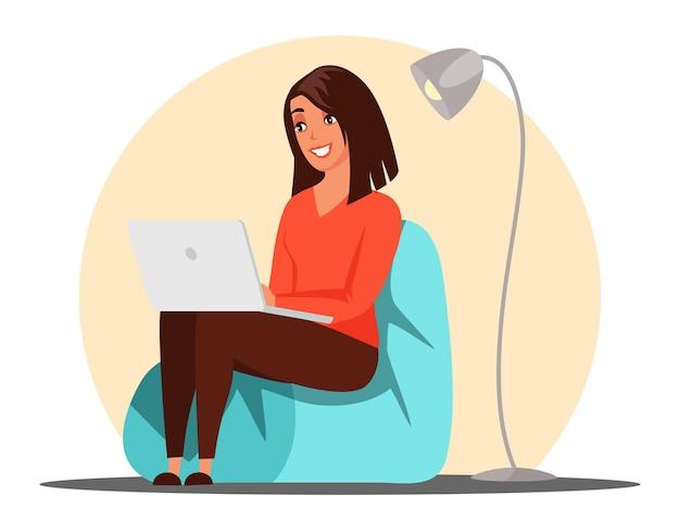 Улыбающаяся молодая женщина, просматривающая на ноутбуке