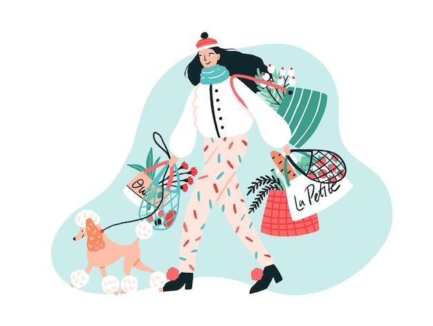 Улыбающаяся молодая женщина, одетая в модную верхнюю одежду, гуляет со своим пуделем на поводке и несет сумки с купленными продуктами