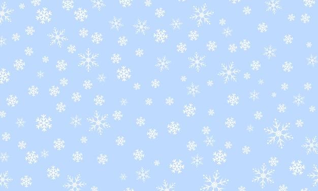 Снежный фон. зимний снегопад. белые снежинки на голубом небе. падающий снег.