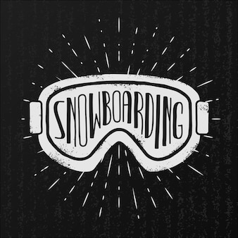 Snowboarding background. goggles and typography on vintage black background.