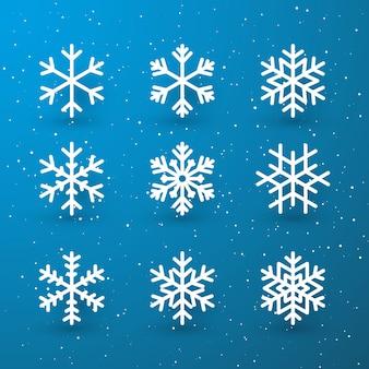 青い背景の上の白い孤立したアイコンシルエットのスノーフレーク冬セット。