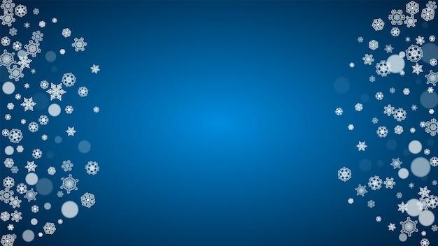 Снежинки падают на синем фоне. рождество и новый год горизонтальная тема. морозные падающие снежинки для баннеров, подарочной карты, приглашения на вечеринку, комплиментов и специального делового предложения