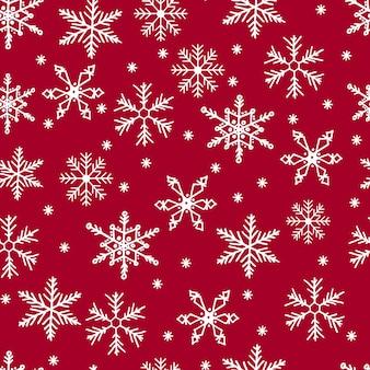 Бесшовный узор из снежинок. белый снег на красном фоне. счастливого рождества.