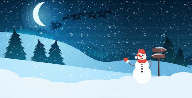 Snowman in hat and scarf waving hand in night pine forest santa flying in sleigh with reindeers in bright starry sky