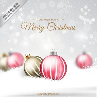 Snowy background with christmas baubles Free Vector