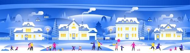居心地の良い町の街のパノラマで人々と雪の夜