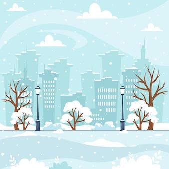 木々の建物の公園と雪の冬の街並み