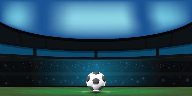 Soccer ball on green stadium in night.