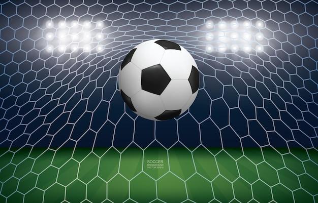 ゴールのサッカーボール。サッカー場のスタジアムの背景にサッカーボールと白いネット。