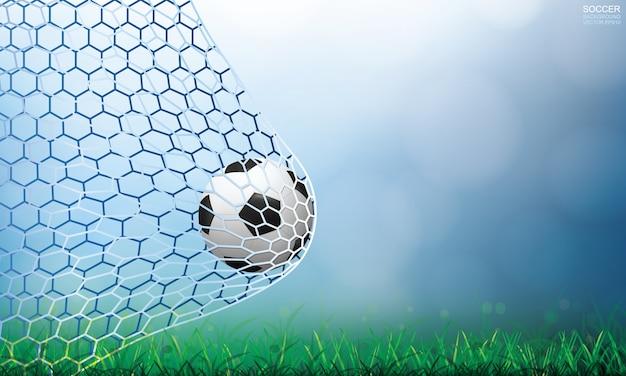 ゴールのサッカーボール。明るいぼやけたボケ味の背景を持つサッカーボールと白いネット。
