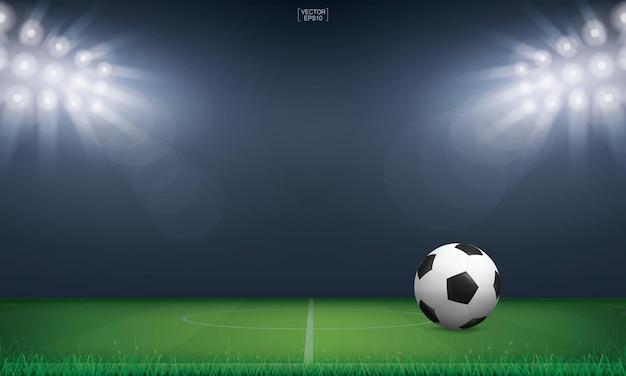 サッカーのサッカーボールとサッカー場のスタジアムの背景の緑の草。ベクトルイラスト。