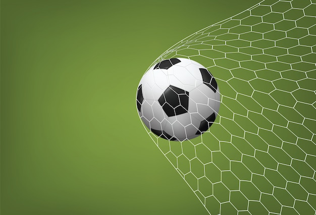 Soccer football ball in goal with white net and green field background