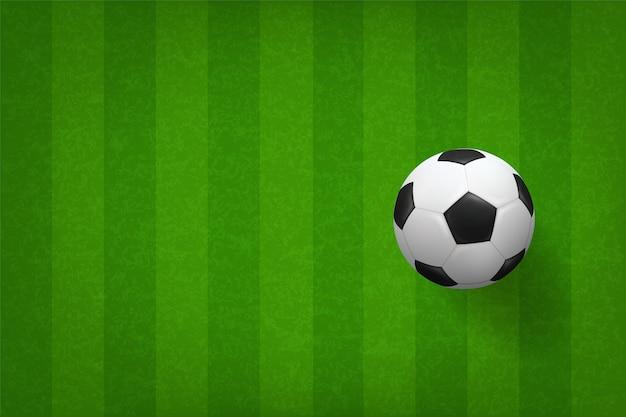 Soccer football ball on green grass field pattern.