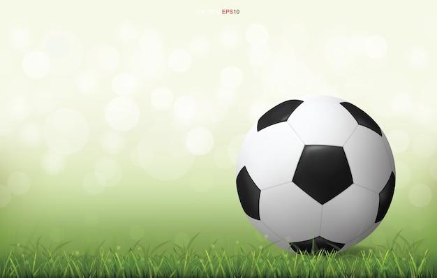Soccer football ball on green grass field with light blurred bokeh background