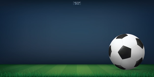Soccer football ball on green grass of soccer field or football field stadium background