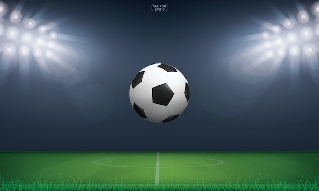 Soccer football ball and green grass of soccer field stadium background