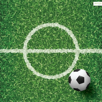 Soccer football ball on green grass of soccer field with center line area.
