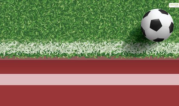Футбольный мяч на зеленой траве футбольного поля с беговой дорожкой для спортивного фона. векторная иллюстрация.