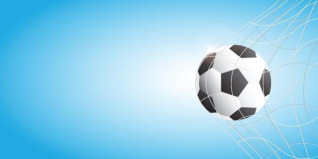 Soccer football in goal net on blue background.