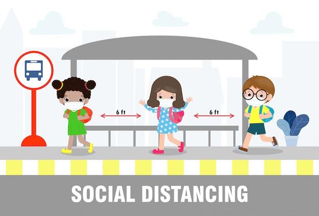 社会的距離の概念、学校に戻って、コロナウイルスまたはcovid-19の間にバス停で医療マスクを身に着けている幸せなかわいい多様な子供たちとさまざまな国籍。新しい通常のライフスタイルの発生。
