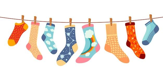 Носки на веревке. хлопковый или шерстяной носок просушите и повесьте на веревку для белья с прищепками. детские носки с текстурами и узорами векторных мультфильмов. иллюстрация шерстяных и хлопковых носков в веревке